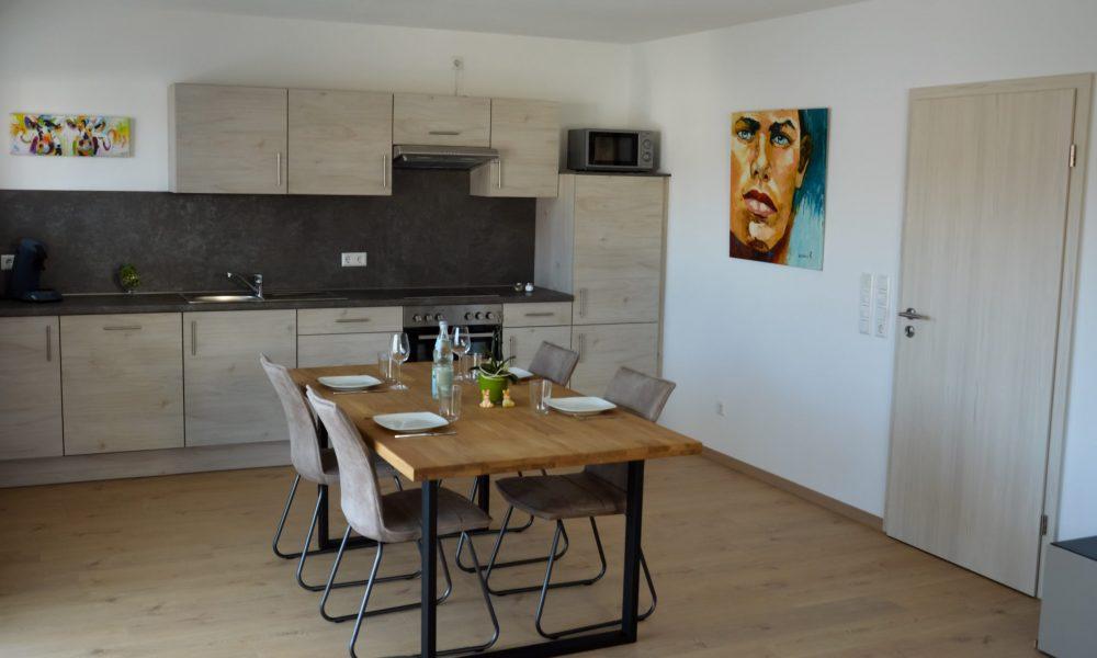 Wohnesszimmer & Küche - Tisch mit voll ausgestatteter Küche im Hintergrund