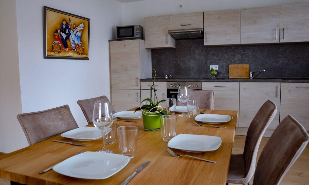 Wohnesszimmer & Küche - Esstisch Nahaufnahme mit vollausgestatter Küche