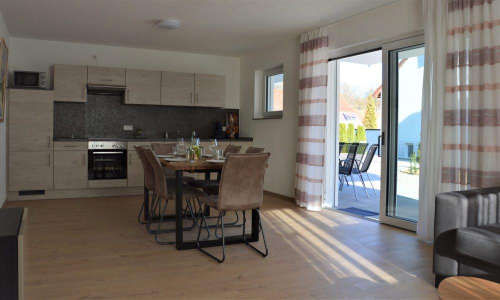 Wohnesszimmer & Küche - Tisch mit voll ausgestatteter Küche im Hintergrund - Terrasse mit Gartenmöbeln