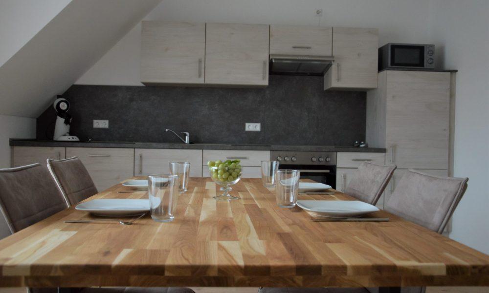 Wohnesszimmer & Küche - Esstisch Nahaufnahme mit voll ausgestatter Küche