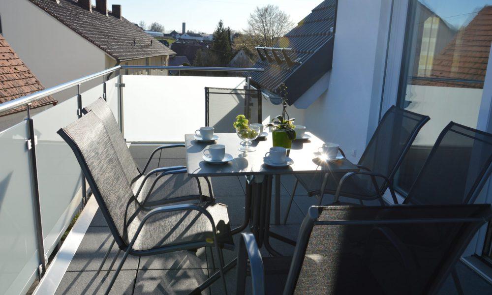 sonnige Nahaufnahme der Balkonidylle bei gedecktem Tisch